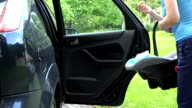 mother open car door and put baby safety chair with infant child video