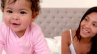 Mother playing with baby daughter on bed video