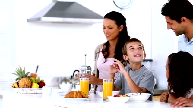 Mother pouring coffee at family breakfast video