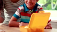 Mother preparing sons lunch box video