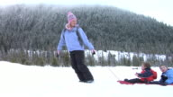 Mother pulling two young boys on sled video