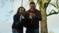 Mother pushing her little boy on the swing while his father takes pictures with his phone video