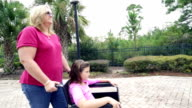 Mother pushing young daughter in wheelchair outdoors video