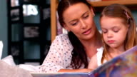 Mother reading a book with her daughter video