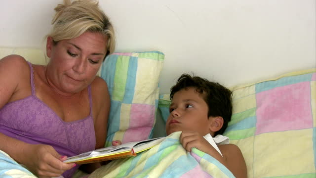 Mother reading to son in bed video