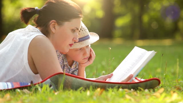 Mother reads a book to his son while on the picnic in the park video