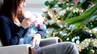 Mother rocking his newborn close to Christmas tree and Snowstorm video