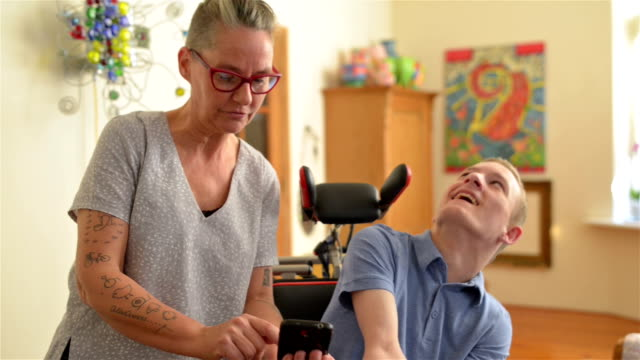 Mother showing funny videos to disabled son video