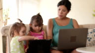 Mother Shows Daughter How to Touch a Tablet Computer video