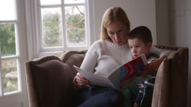 Mother Sits In Chair At Home Reading Book To Son Shot On R3D video
