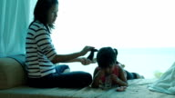 Mother sitting at sofa and combed her daughter 's hair. video