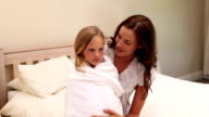 Mother sitting with her little girl in a towel video