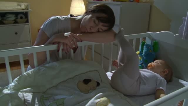 HD CRANE: Mother Sleeping Beside Sleepless Baby video