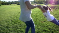 SLO MO Mother spinning her daughter in sunny meadow video