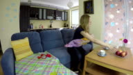 Mother swing newborn baby on hands sit on sofa and eat apple. video