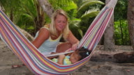 Mother swings young girl in hammock at beach video