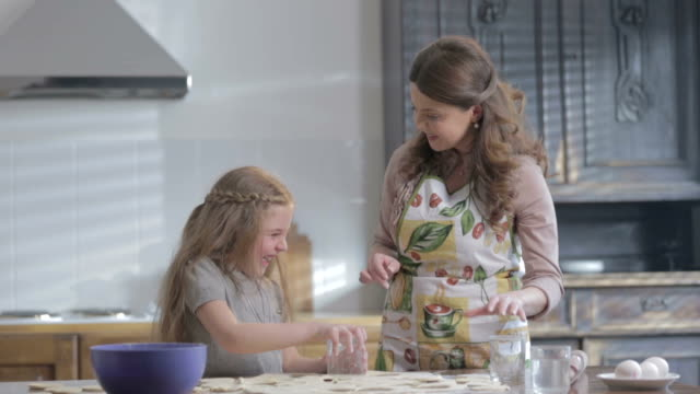 Mother Teaching Daughter How To Cook. Mother and happy daughter having fun while cooking together in kitchen at home. video