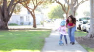 Mother Teaching Daughter To Ride Scooter video