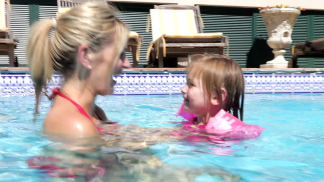 Mother Teaching Daughter To Swim In Pool video