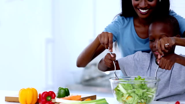 Mother teaching to her son how mix salad video