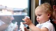 Mother traveling by train with her baby. Mom and toddler baby sitting next to train window. Mom adjusting baby clothes video