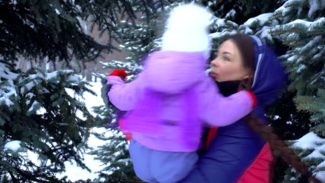 mother turns the baby in her arms near snowy trees video