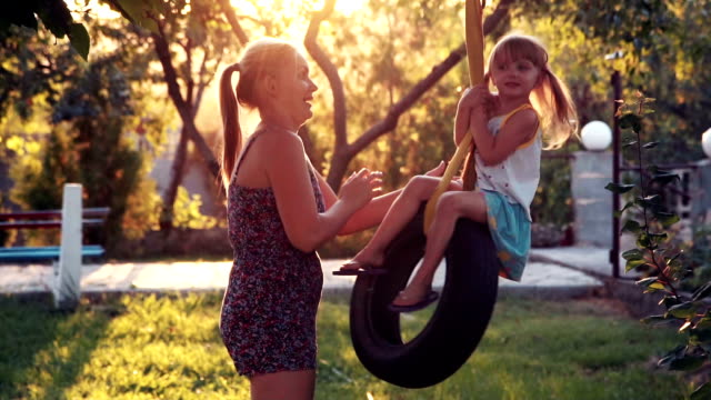 Mother twists the little daughter on a swing video