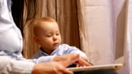 Mother typing while holding baby video