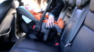 mother unfasten safety belts on child in car seat. FullHD video