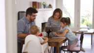 Mother Uses Laptop Whilst Father Plays With Children At Home video