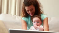 Mother using laptop with baby son on her lap video