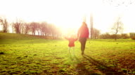 Mother walking with cute disabled child in park at sunset video