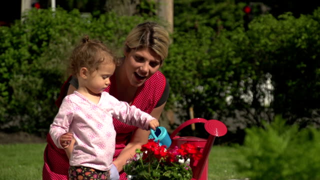 Mother watering flowers with her daughter video