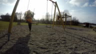 mother with baby daughter girl swing in park. video