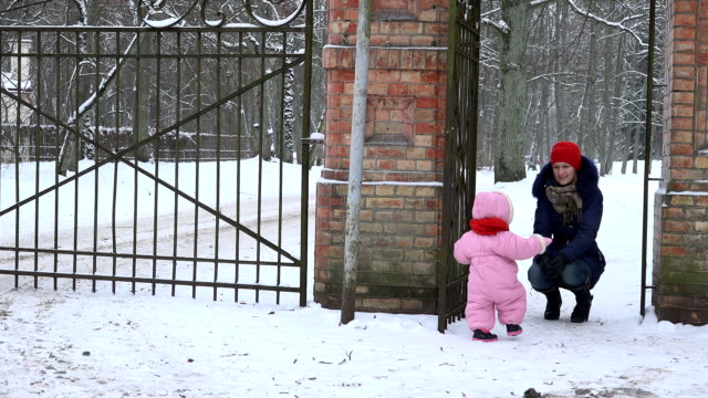 mother with baby daughter girl walk through retro gate in snowy winter park. video