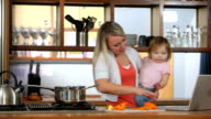 Mother with baby in kitchen multi-tasking video