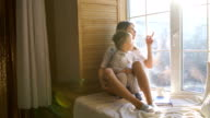 Mother with baby sitting at the window and play video