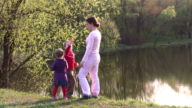 mother with children on spring pond video