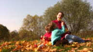 Mother with children sit in autumn leaves video