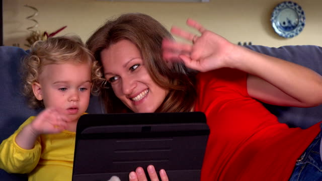 mother with daughter blow kiss to father on tablet video conversation video