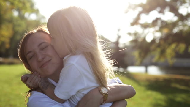 Mother with daughter hugging and kissing at nature at sunset video
