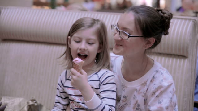 Mother with daughter in cafe. Eating ice-cream, talking, having fun video