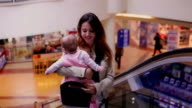 Mother with her baby at the escolator in Shopping Mall video