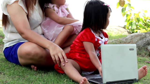 Mother with her daughter plaing notebook in  park. video