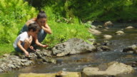 Mother with her son are sitting near a stream video