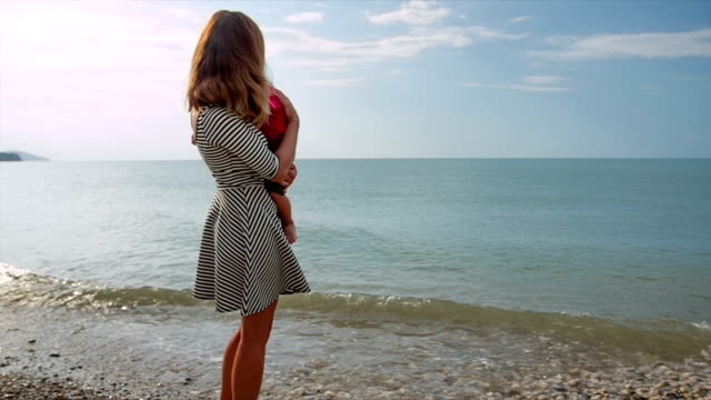 Mother with her son in her arms against the sea video