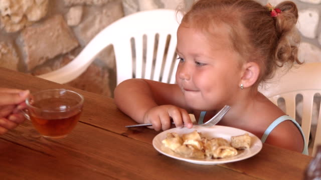 Mother with his little daughter eating in outdoor summer kitchen beside house video