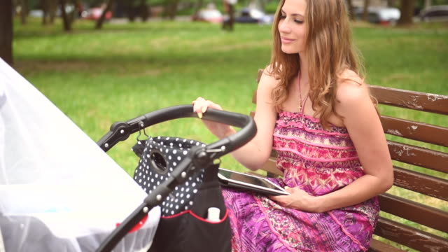 Mother with pram in the park on a sunny day video