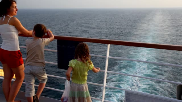 Mother with son and girl stands on deck of ship video