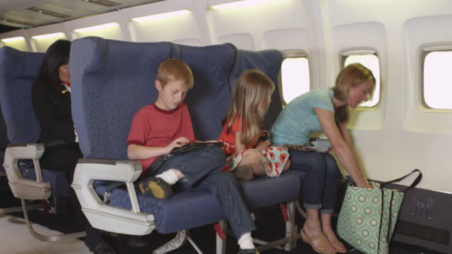 Mother with two small children on plane video